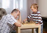 Vater verliert gegen Sohn beim Schach spielen